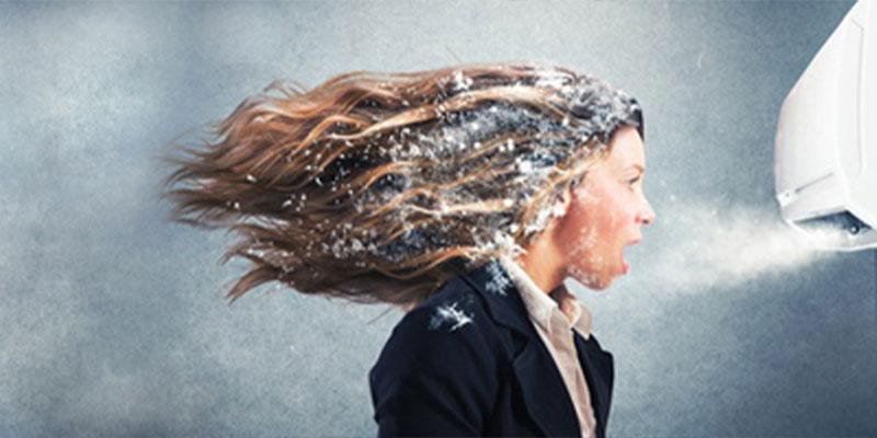 Kälte-Systeme Frau vor einer Klimaanlage aus der Schnee fliegt as Darstellung für Klima