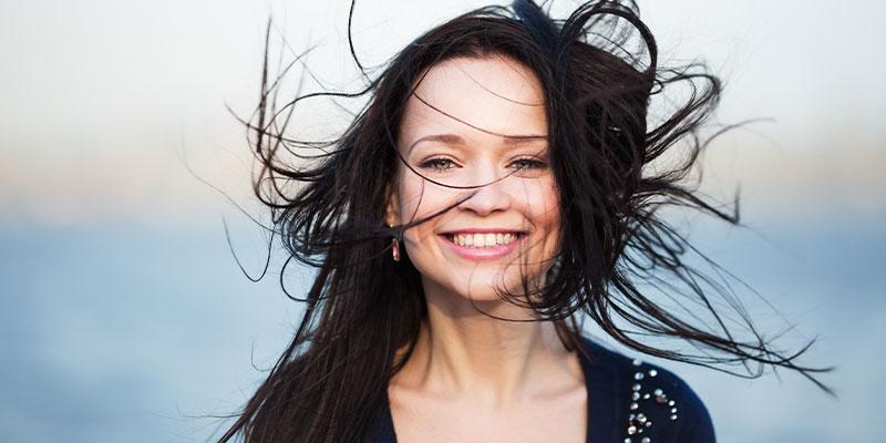 Kälte-Systeme Frau im Wind mit zerzausten Haaren als Darstellung für Lüftungstechnik