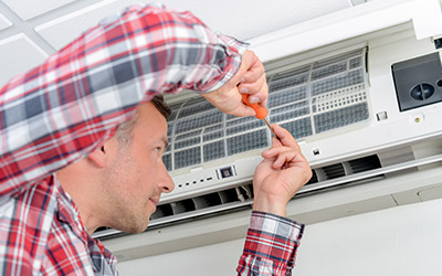 Mann bei der Reparatur der Klimatisierung-Anlage